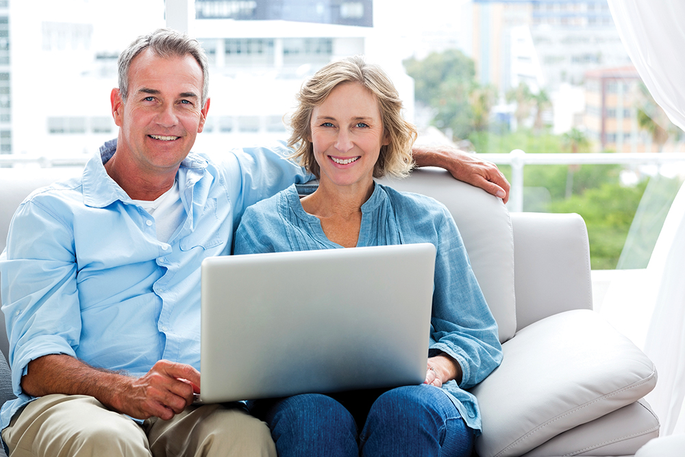 Couple in their 50's sitting with a laptop