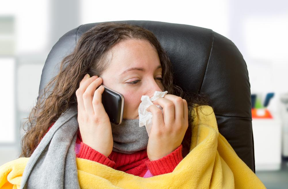 sick woman in blanket sitting with tissue